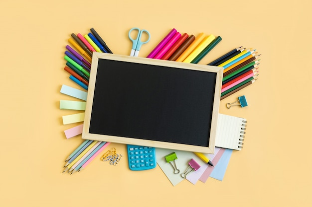 学校用品のコピースペースの色の背景上の文房具機器学校のコンセプトに戻る