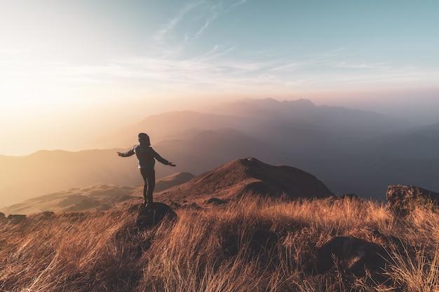 Молодой человек путешественник ищет красивый пейзаж на закате на горе