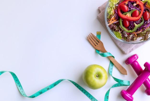 Свежий салат с зеленым яблоком, гантели и измерительная лента на белом фоне.