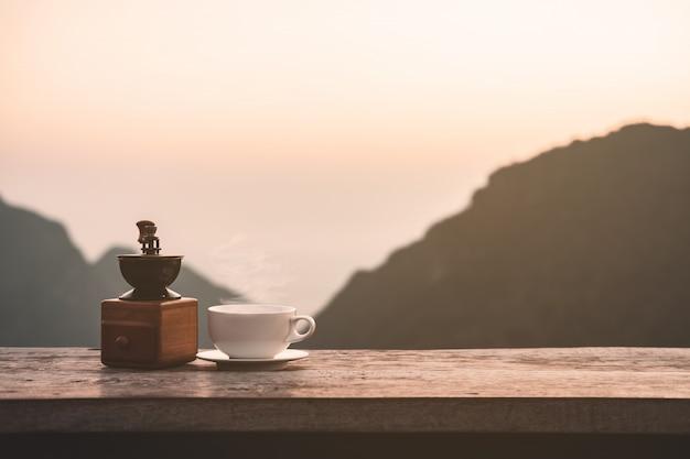 Горячая утренняя чашка кофе с фоном гор на рассвете с копией пространства