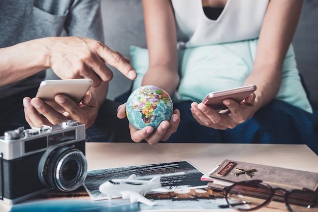 若いカップル休暇旅行を計画し、情報を検索またはスマートフォンでホテルを予約する