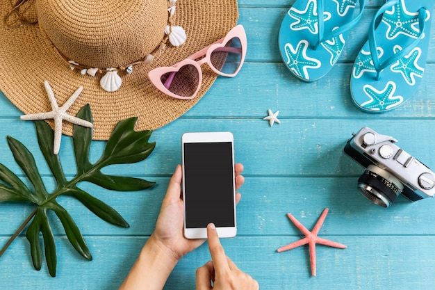 木製の背景、夏の休暇の概念上のスマートフォンとアクセサリーアイテムを旅行します。