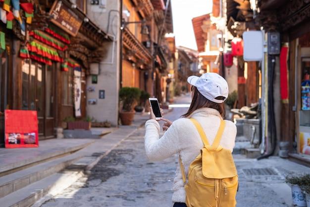 シャングリラの旧市街を歩いて、場所、旅行ライフスタイルを検索するためのスマートフォンを使用して若い女性旅行者