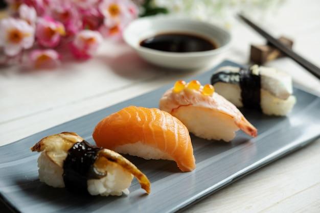 白い木製のテーブルに醤油入り刺身寿司のクローズアップ