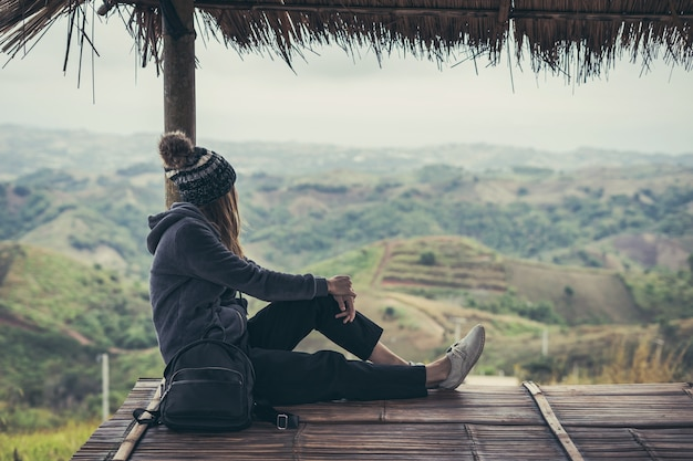 Молодая женщина путешественник сидит и смотрит взгляд на природу