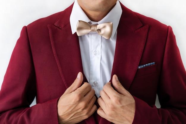 蝶ネクタイと赤いスーツを着ている若い男