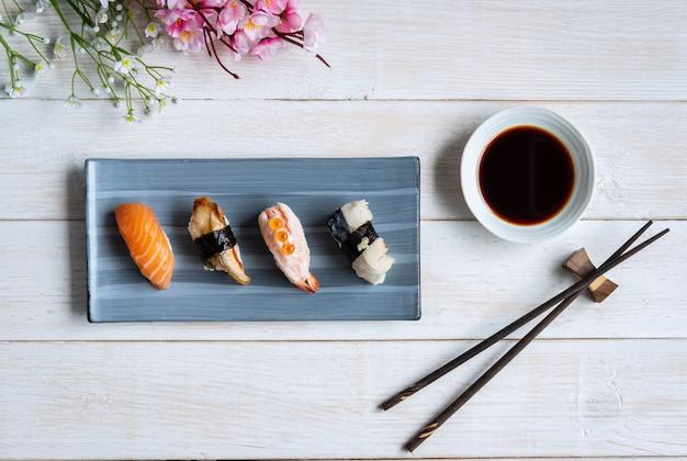 白い木製テーブル、上面に醤油入り刺身寿司