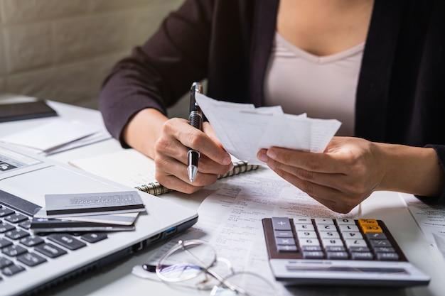 手形、税金、銀行口座の残高を確認し、自宅の居間で費用を計算する若い女性を強調