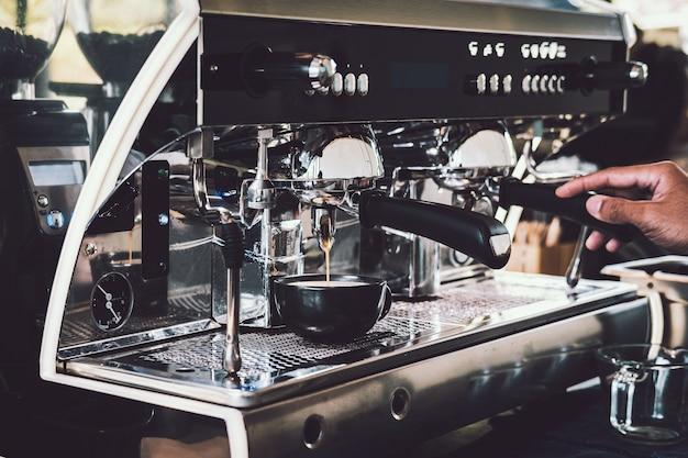 カフェでプロのコーヒーマシンでコーヒーを作るバリスタ