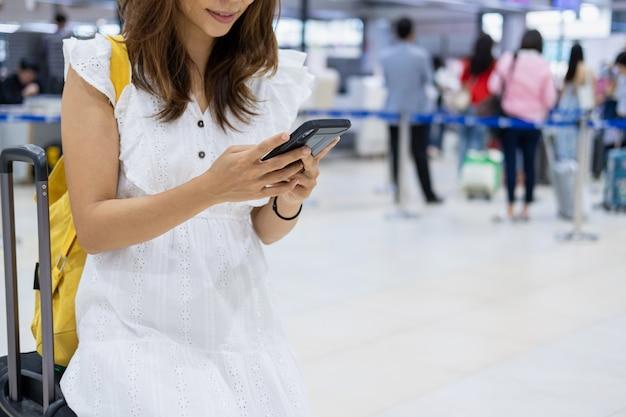 Молодая женщина путешественник с помощью своего смартфона, чтобы проверить рейс в аэропорту