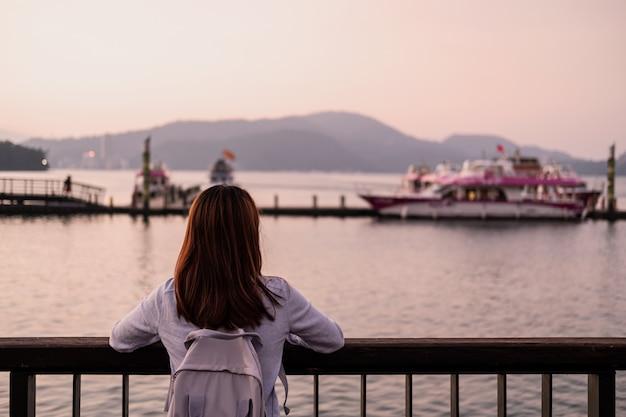 Путешественник молодой женщины смотря красивый ландшафт на озере луны солнца в тайване, концепции образа жизни перемещения