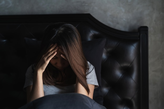 孤独な若い女性が落ち込んで、暗い寝室、否定的な感情の概念に座って強調