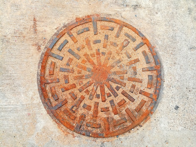 Старый ржавчинный металл крышки дренажного шланга с бетонным полом