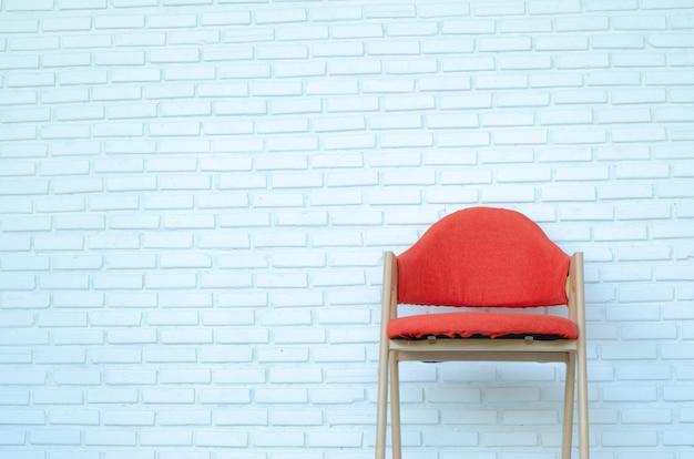 Красный стул на белой предпосылке кирпича, современной комнате, космосе экземпляра.