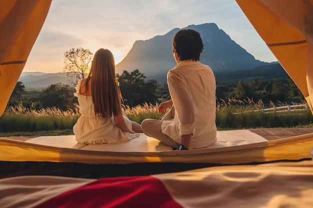 屋外キャンプを楽しむアジアカップル自然の中で夕日を見て