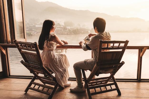 アジアのカップルがリー・ワイン・ラック・タイ、中国人居留地、メーホンソン、タイで紅茶の日の出を飲む