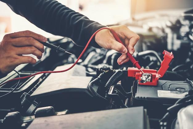 Техник руки автомеханика, работающего в автосервисе сервисное и техническое обслуживание автомобильного аккумулятора