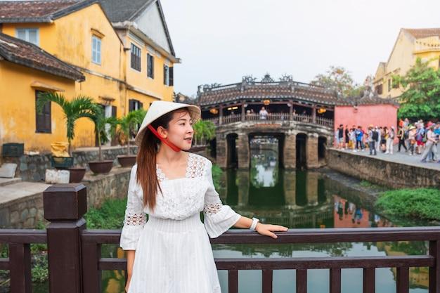 日本の屋根付き橋を持つ旅行女性