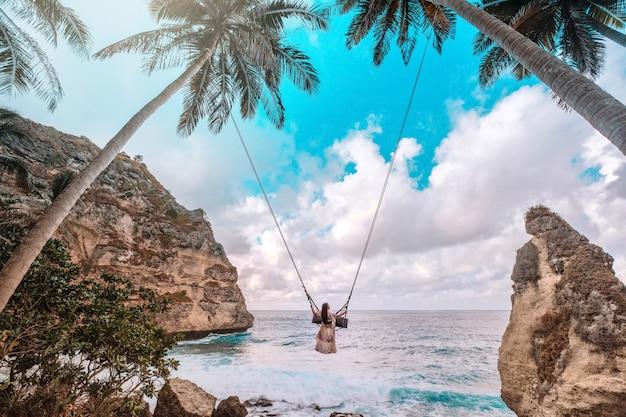 Красивая девушка на качелях кокосовых пальм на пляже на пляже даймонд, остров нуса пенида, бали, индонезия