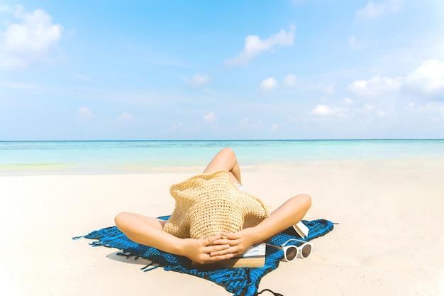 夏のビーチでの休暇の女性は自由時間にビーチでリラックスします。