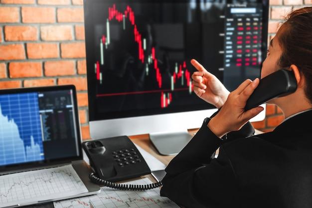 ビジネスの女性の取引投資家の株式市場は、株式市場の概念を取引グラフ株式市場を議論します。