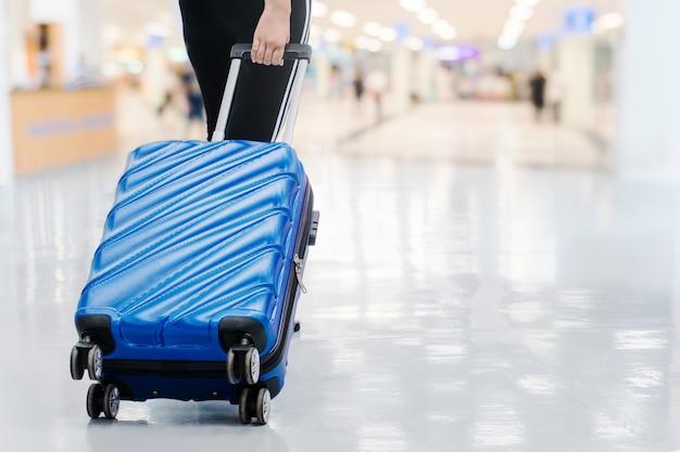 旅行者の女性と空港ターミナルでの荷物旅行のコンセプト