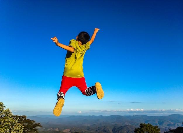 自然に飛ぶ幸せな若い少年のライフスタイルのイメージ。