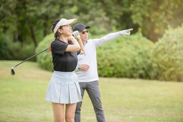 Молодой азиатский женщина-гольфист делает практику с ее профессиональным тренером по гольфу