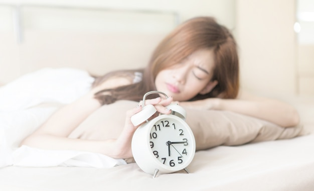 Молодая красивая уставшая и ленивая женщина пытается проснуться и выключить будильник