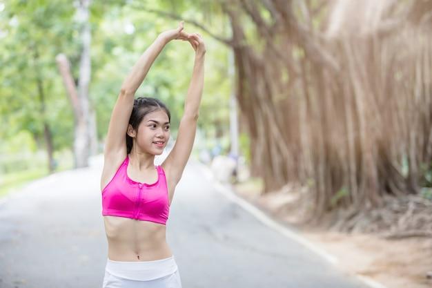 アジアの若い女性が公園で運動をした後の体をストレッチ