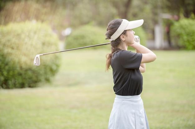 アジアの女性のゴルフプレーヤーのフェアウェイでスイングゴルフクラブ