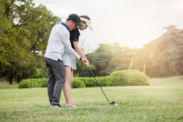 Молодой азиатский гольфист женщины практикует с ее профессиональным тренером по гольфу в гольф-клубе