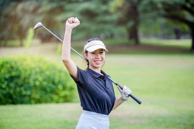 ゴルフボールを穴に入れた後ゴルフボールを示す若い幸せなアジア女性ゴルファー
