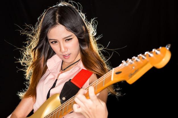 Молодая и красивая рок-девушка играет на электрогитаре