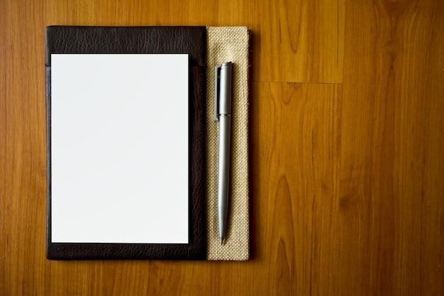 Кожаный блокнот с бумагой и ручкой на деревянный стол