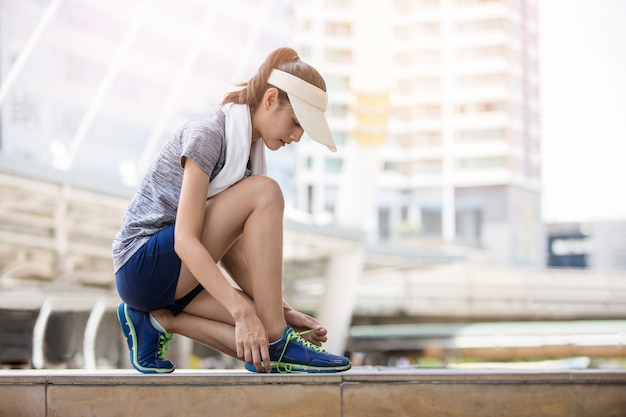 Привлекательная спортсменка завязывает шнурки и готовится к бегу в городском городе