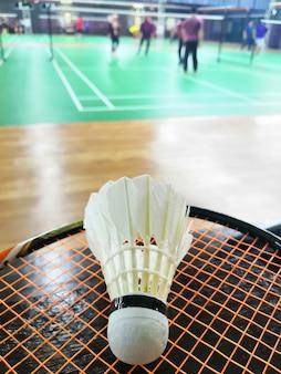 ぼやけたバドミントンコートの背景を持つラケットにスポーツコンセプトバドミントン羽根