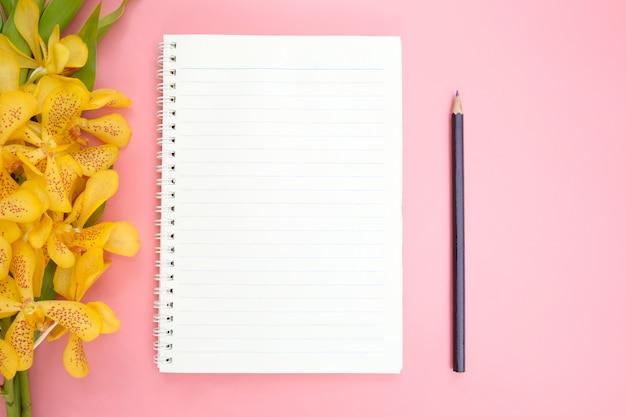 ピンクの開いているノートブック紙の平面図またはフラットレイアウト。