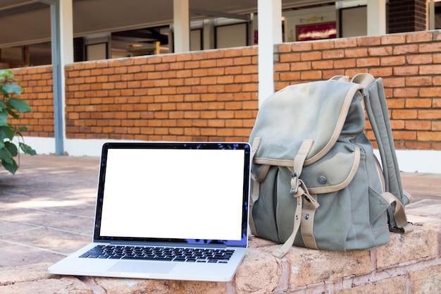 Пустой экран ноутбука и сумки.