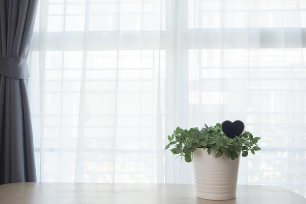 白いカーテンの窓の背景に緑の庭の花と木製のテーブル。