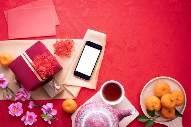 赤の背景に中国の旧正月の組成を持つ空白の画面スマートフォン。