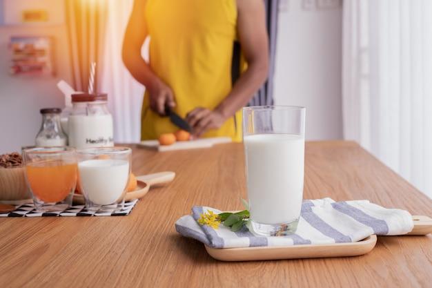 健康的な朝食のテーブルのための食糧を準備する人間とミルクのガラス。