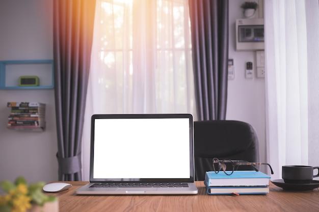 ノートパソコン、ノートブック紙、リビングルームでコーヒーカップに空白の画面を持つ木製のテーブル。