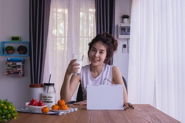 アジアの若い女性と朝食用のテーブルは、リビングルームでいくつかの牛乳を飲みます。