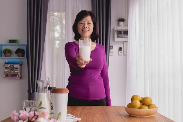 アジアの高齢者女性と一緒に朝食用のテーブルは、自宅でミルクのガラスを保持します。