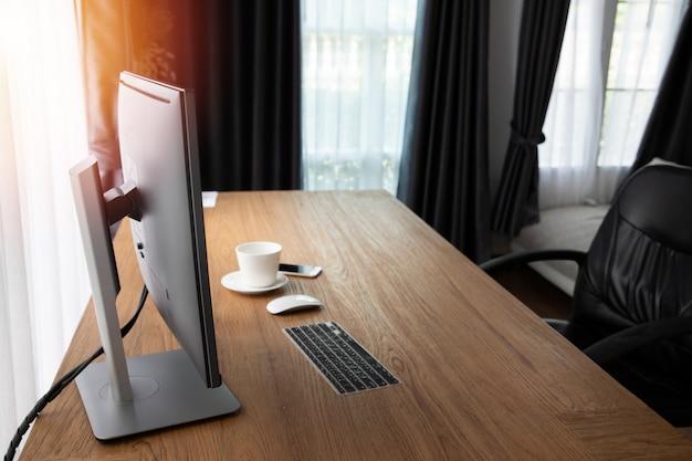 作業室のモニターコンピューターとコーヒーカップの木製オフィステーブル