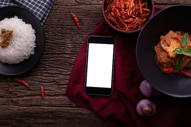 スマートフォン、タブレット、携帯電話、乾燥赤豚肉ココナッツカレーの空白の画面を持つキッチンテーブル。