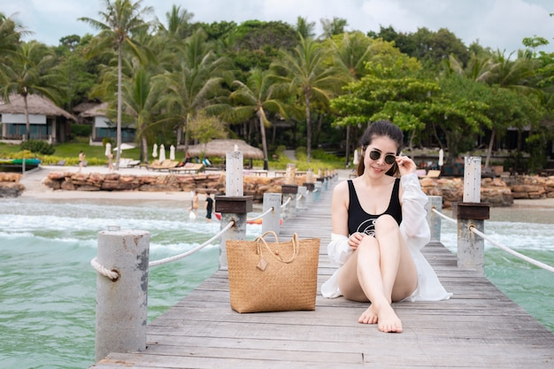 海を背景に木の橋の上に座っている水着で笑顔の若いアジア女性。夏休みのコンセプトです。