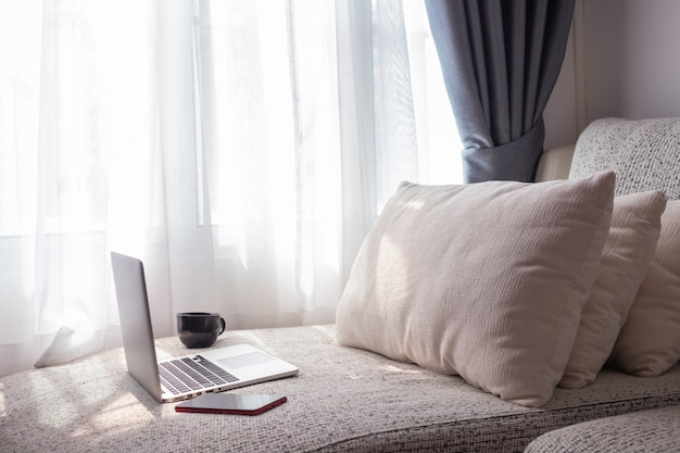 ノートパソコンの空白の画面と寝室の目覚まし時計付きの白いベッド。