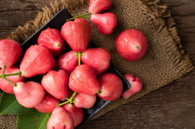 アジアのトロピカルフルーツの木のテーブルにピンクのバラアップル。